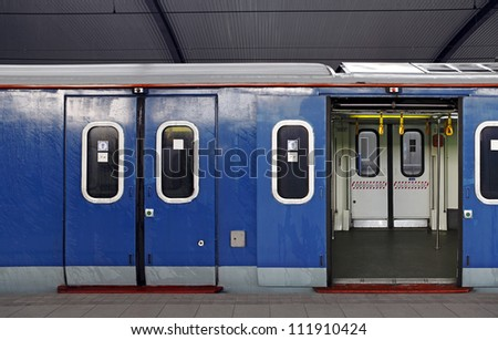 A blue train carriage with open and closed sliding mechanical door at a train station platform. - stock photo