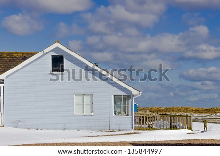 A blue weather-boarded holiday home, next to the beach, after snowfall.