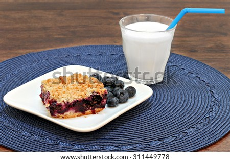A blueberry streusel cookie and a glass of milk for a healthy tasty snack. - stock photo