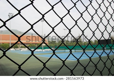 a blur picture of Badminton court behind the wire mesh
