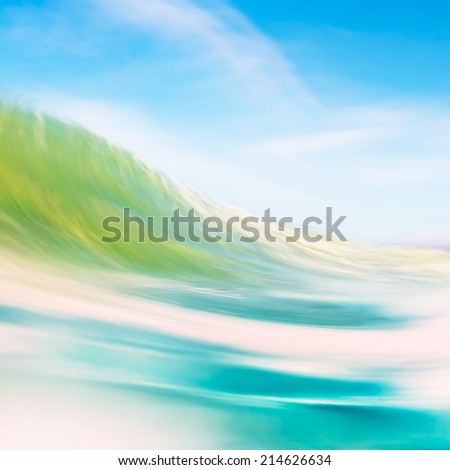 A blurred abstraction of a wave and flowing surf about to break onshore.  Image made with panning motions combined with a long exposure. - stock photo