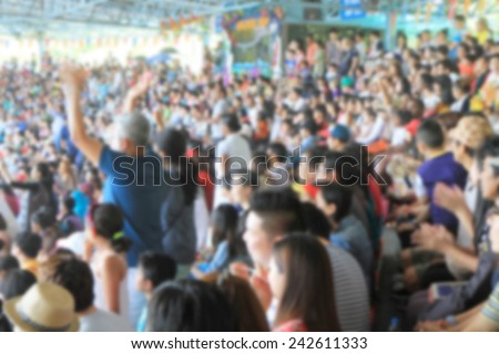 A blurred Asian crowd in a stadium