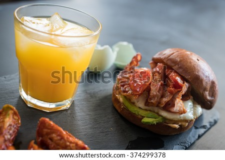 A blurred bacon and egg roll with juice. - stock photo