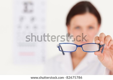 A blurred female optician showing glasses - stock photo