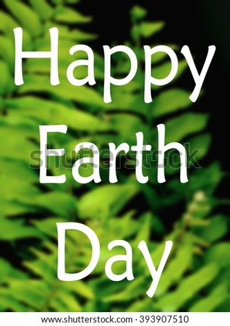 A blurred image of green fern fronds on black background for Earth Day on April 22 with text added - stock photo
