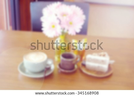 a blurred of a cup of coffee latte and delicious  coffee cake - stock photo