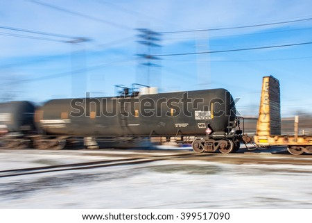 A blurred view of a tank car racing across railway tracks. - stock photo