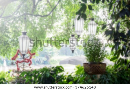 A blurred vintage lanterns on big tree with green plants background