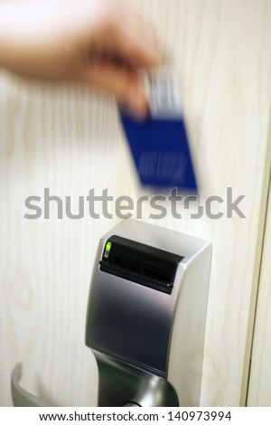 A blurry hand with a keycard, opening the electronic lock on a hotel door, high iso - stock photo