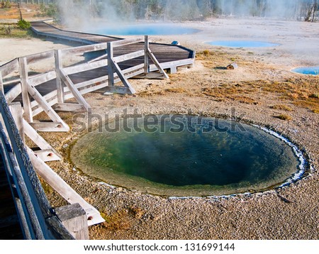 A board walk meanders through the steaming thermal pools of West Thumb Geyser Basin in Yellowstone National Park, Wyoming. - stock photo
