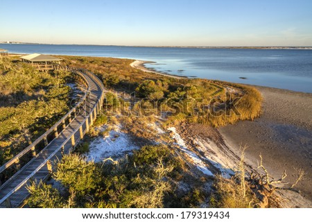 A boardwalk curves over the vegetation on the dunes in Big Lagoon State Park near Pensacola, Florida - stock photo