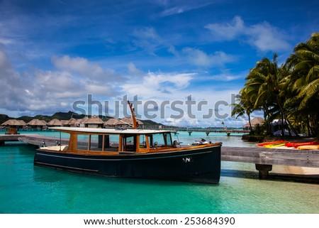A Boat at a Dock on the Beach in Bora Bora - stock photo
