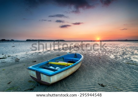 A boat at sunset on the beach at Sandbanks in Poole, Dorset - stock photo