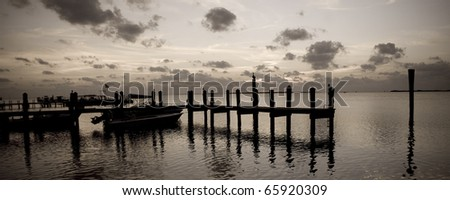 A boat dock at sunset in Key Largo Florida (sepia/panoramic). - stock photo