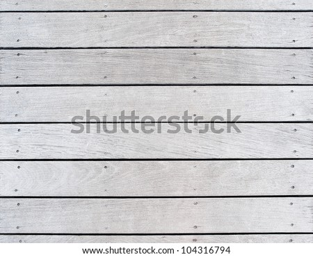 A boat dock's old weathered and faded wood decking. Features the pattern and texture of the wood and hardware fasteners. - stock photo