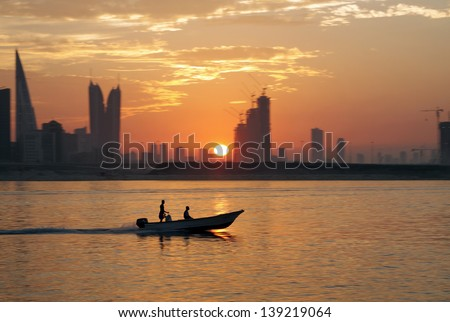 A boat during sunset with Bahrain highrise buildings - stock photo