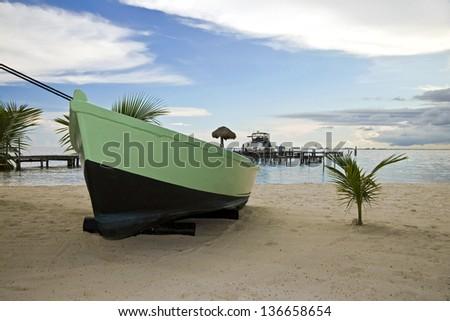 A boat in a Beach of Isla Mujeres, Mexico. Barco encallado en Isla Mujeres en un día soleado con cielo nublado. - stock photo
