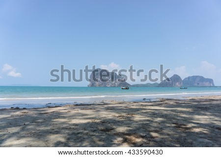 A boat in the beautiful sea and blue sky at Pakmeng beach with tree's shadow in Trang, Thailand.