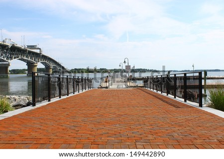 A boat landing along the Yorktown riverwalk landing on the York river in Yorktown VA with the Coleman bridge and York river in the background - stock photo