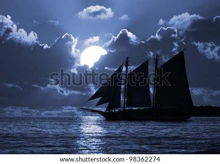 A boat on the moonlit seas. Possible pirate theme. - stock photo