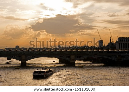 A boat on the River Thames passes below Blackfriars Bridge in London. The bridge has installed 4,400 solar panels on the roof creating the biggest solar bridge in the world. - stock photo