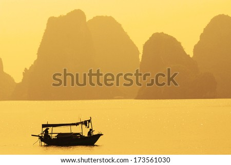A boat sailing along the coast of Halong Bay, Vietnam - stock photo