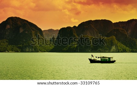 A boat sailing along the coast of Halong Bay, Vietnam. - stock photo