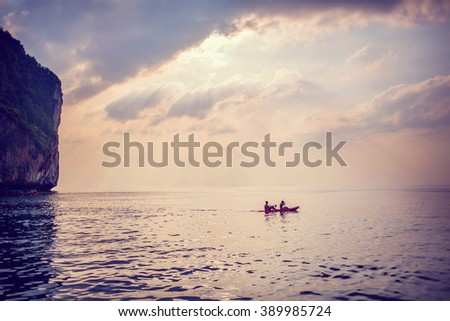 A boat sailing under beautiful sun ray at sunset in gorgeous Maya bay, Phi-Phi, Thailand. Image with selective focus and toning - stock photo