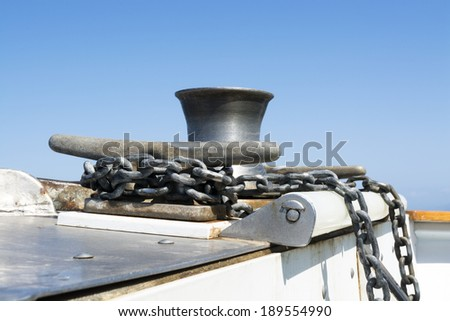 A boats anchor chain is wrapped and secured around a steel cleat as the boat motors across the ocean. - stock photo