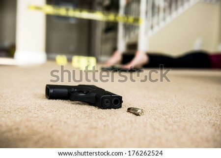 a body on the ground of a crime scene with a gun in the foreground. - stock photo