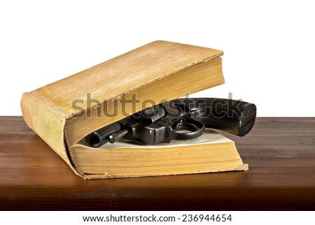a book with handgun on the table - stock photo