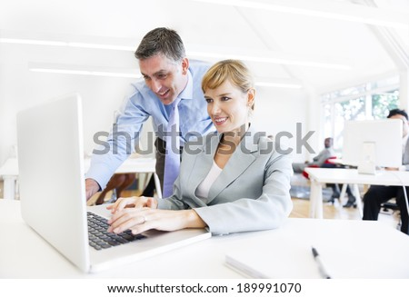 A Boss Assisting his Employee in Front of the Laptop - stock photo