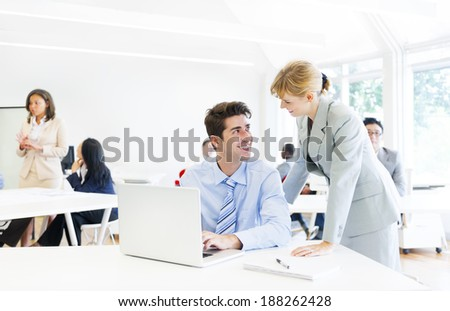 A Boss Guiding her Employee in Front of the Laptop - stock photo