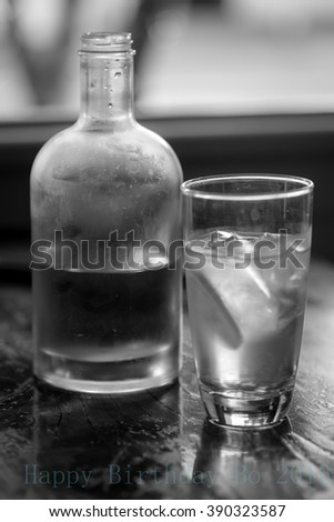 A bottle and a glass of water in black and white