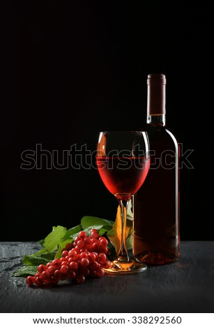 A bottle and a glass of wine, red grapes, on grey-black background - stock photo