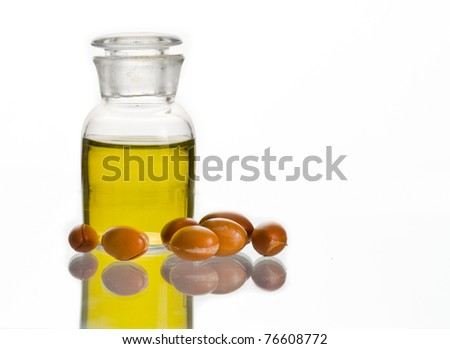 A bottle of argan oil and some argan fruits on white. Argan oil is used for cosmetic products - stock photo