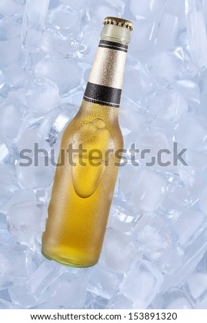 A bottle of blonde beer on ice. - stock photo