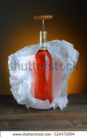 A bottle of blush wine wrapped in tissue paper, on a rustic wood surface and a light to dark warm background. A vintage cork screw is inserted in the bottle. - stock photo