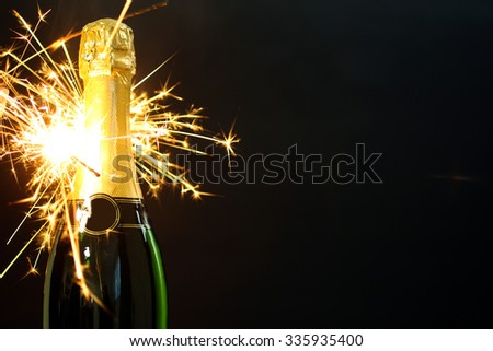 a bottle of champagne and sparklers isolated on gray background - stock photo