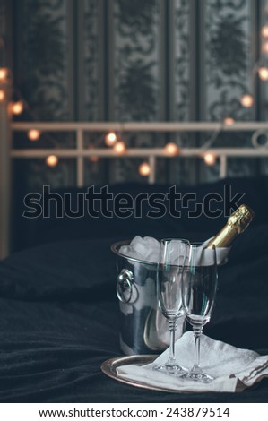 A bottle of chilled champagne in an ice bucket and two glasses on a bed, dark tones - stock photo