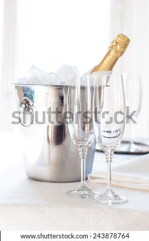 A bottle of chilled champagne in an ice bucket and two glasses on a white tablecloth, luxurious celebration, bright daylight - stock photo