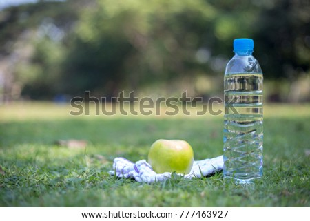 A bottle of drinking water, towel and green apple on a green grass, healthy concept