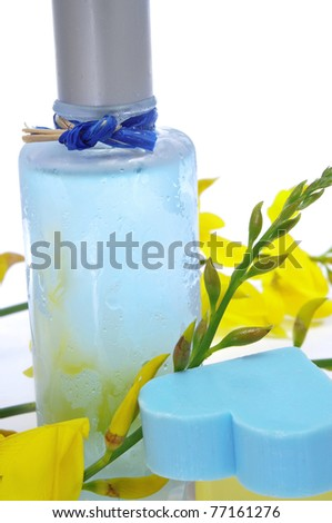 a bottle of fresh scent with flowers and heart-shaped soap on a white background - stock photo