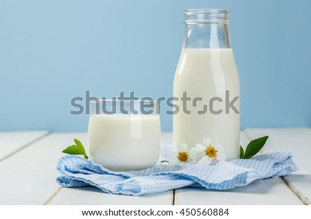 A bottle of milk and glass of milk on a white wooden table on a blue background