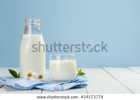 A bottle of milk and glass of milk on a white wooden table on a blue background, tasty, nutritious and healthy dairy products - stock photo