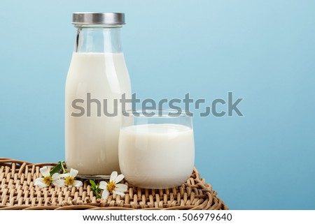 A bottle of milk and glass of milk on a wicker table on a blue background