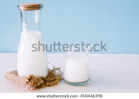 A bottle of milk and glass of milk on wooden table - stock photo