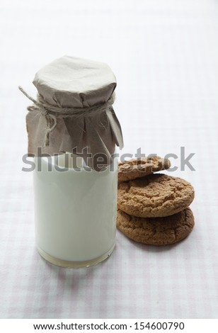 A bottle of milk and oatmeal cookies on the table with a tablecloth in a pink cell - stock photo
