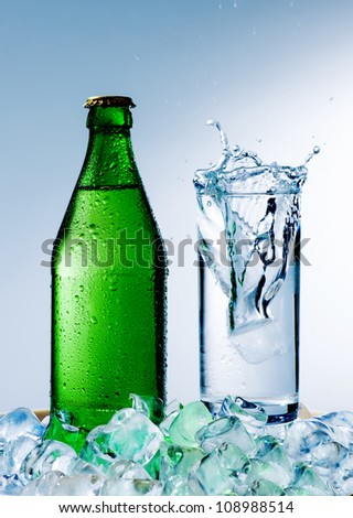 A bottle of mineral water with ice and a glass on a blue background - stock photo