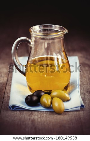 A bottle of olive oil and olives on old wooden background, selective focus - stock photo